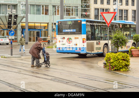 Old woman with wheeled walker and other people cross over a road with tram rails, behind a public bus in the city - Stock Photo