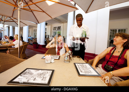 Guests ordering drinks on the terrace, the Victoria Falls Hotel, Zimbabwe Africa - Stock Photo