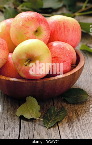 Red ripe apples in bowl on a wooden table - Stock Photo