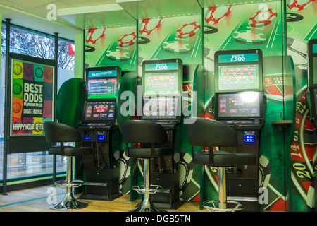 Gaming machines (FOBT fixed odds betting terminal) in Paddy Power Betting office. England, UK - Stock Photo
