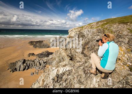 A female photographer above Porth Joke on Pentire Point, near Newquay, Cornwall, UK. - Stock Photo