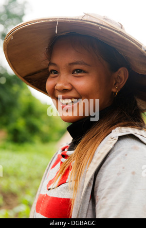 Young woman takes a break from tending her corn crop. - Stock Photo