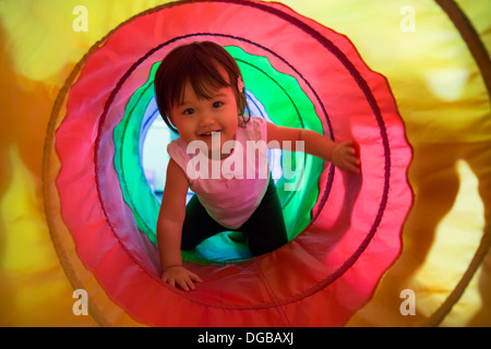 Baby girl crawling through play tunnel - Stock Photo