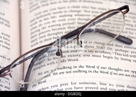 Pair of glasses laying on top of an open book. - Stock Photo