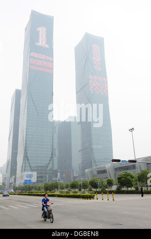 Huge brand new skyscrapers for lease in China; in the foreground a person rides an electric motorcycle through the - Stock Photo