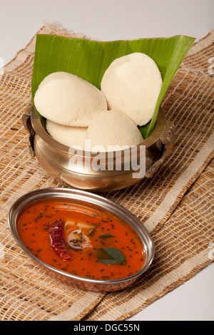 Idli is a South Indian breakfast dish served on banana leaf - Stock Photo