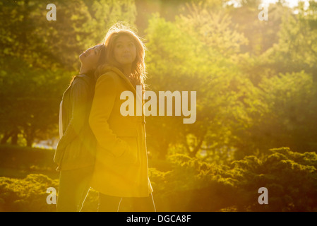 Two young women standing back to back in park - Stock Photo