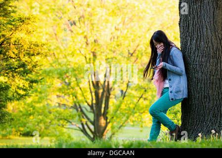 Young female laughing at mobile phone in park - Stock Photo