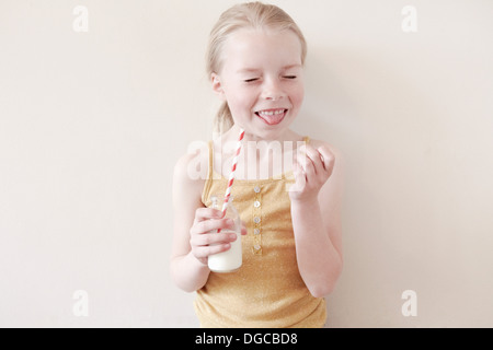 Young girl sticking tongue out and holding glass of milk - Stock Photo
