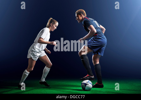 Male and female soccer players defending ball - Stock Photo