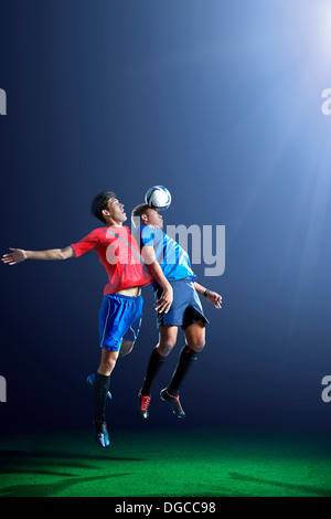 Male soccer players heading ball - Stock Photo