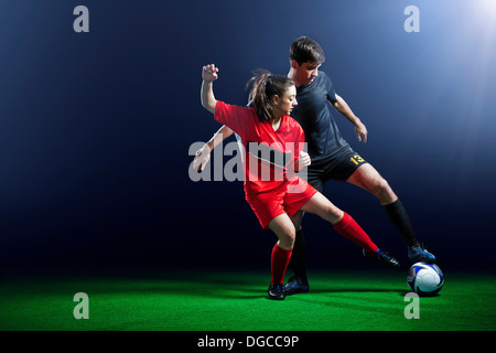 Male and female soccer players in action - Stock Photo