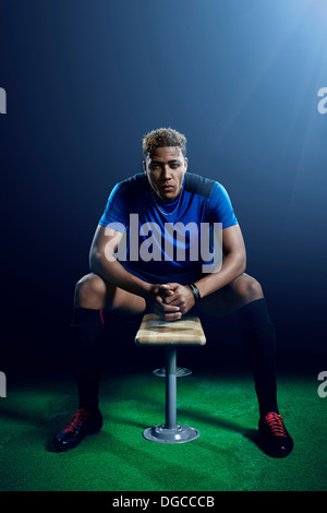 Portrait of young male soccer player on bench - Stock Photo