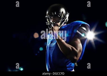 Portrait of american football player wearing helmet - Stock Photo