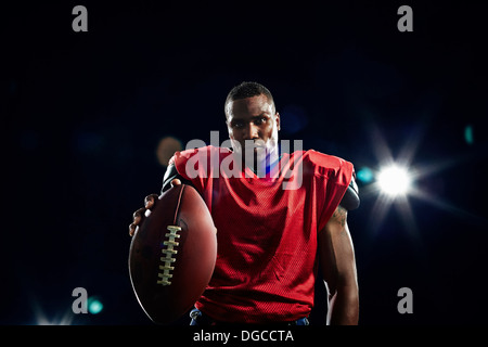 Portrait of american football player holding ball - Stock Photo