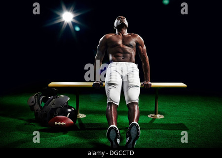Portrait of american football player doing push ups - Stock Photo