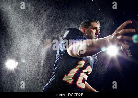 American footballer running with ball - Stock Photo