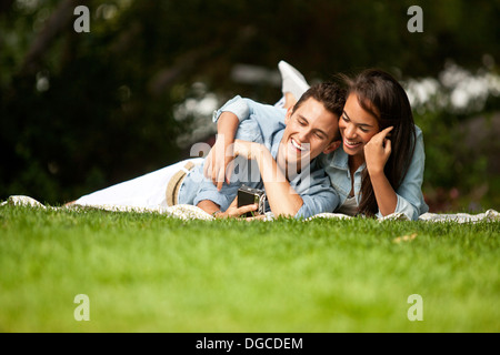 Young couple lying in park, smiling - Stock Photo