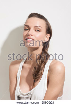 Young woman wearing vest and smiling, portrait - Stock Photo