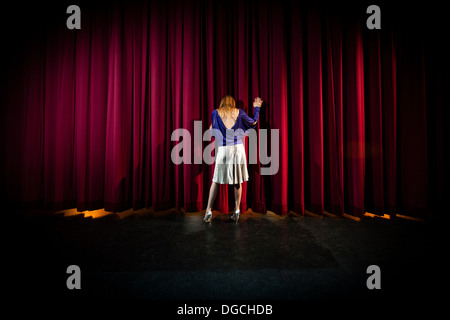 Mature woman standing in theatre stage, rear view - Stock Photo