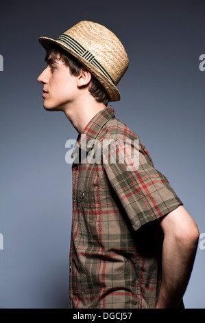 Young man wearing hat and short sleeved shirt, profile - Stock Photo