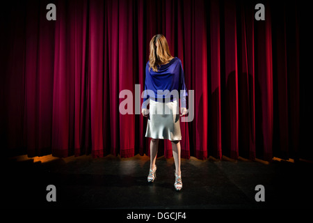 Mature woman standing in theatre stage with hair covering face - Stock Photo