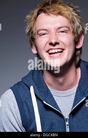 Young man in laughing in studio, portrait - Stock Photo
