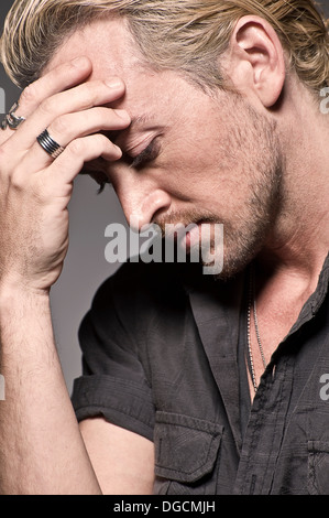 Young man with head in hands, studio shot - Stock Photo