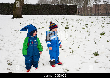 two toddlers having fun playing in park blizzard - Stock Photo