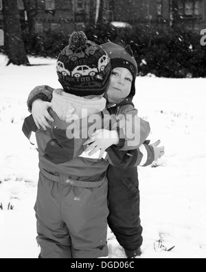 toddlers hugging in the snow - Stock Photo