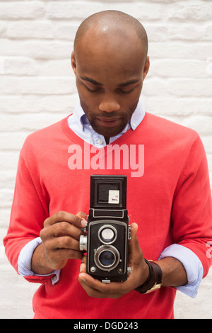 Portrait of young man using twin lens reflex camera - Stock Photo