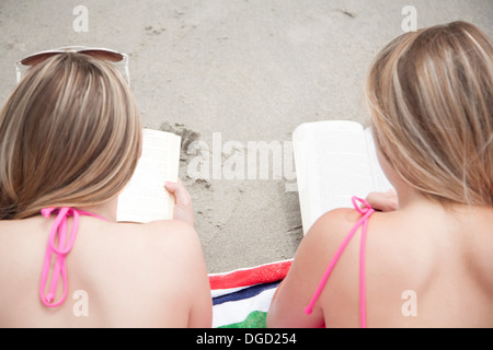 Young women reading books on beach - Stock Photo