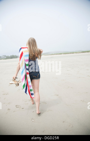 Young woman walking on beach with towel - Stock Photo