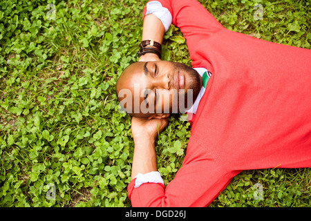 Portrait of young man lying on grass - Stock Photo