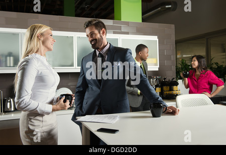 Young business colleagues chatting in office kitchen - Stock Photo