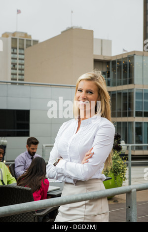 Young businesswoman smiling, portrait - Stock Photo