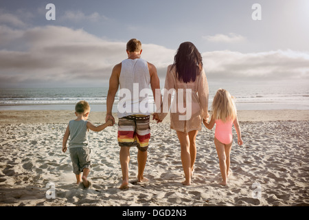 Young family holding hands together on beach, rear view - Stock Photo