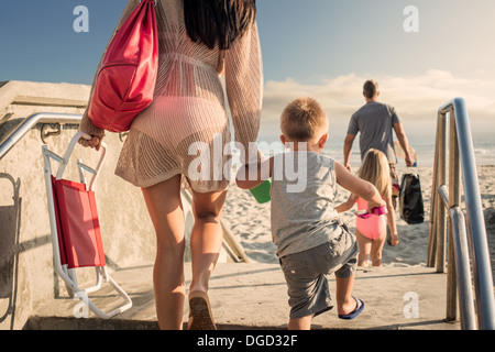 Young woman arriving at beach with son - Stock Photo