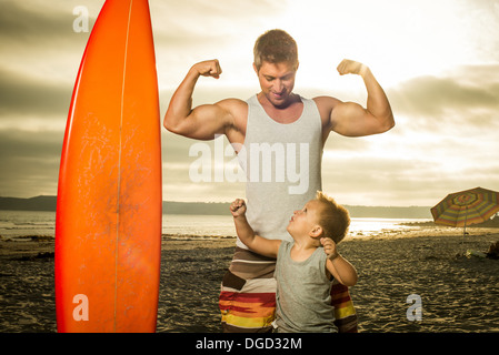 Young man and son flexing muscles on beach - Stock Photo