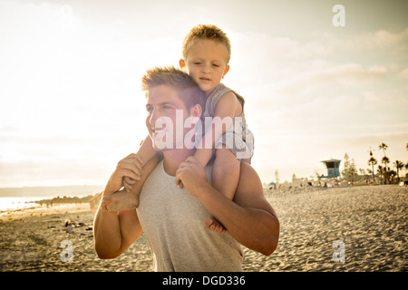 Young man carrying son on shoulders on beach - Stock Photo