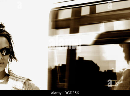 20 years old girl standing infront of skytrain speeding by. Vancouver BC Canada - Stock Photo
