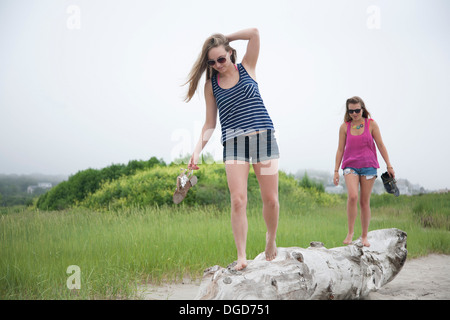 Young women walking along log on beach - Stock Photo