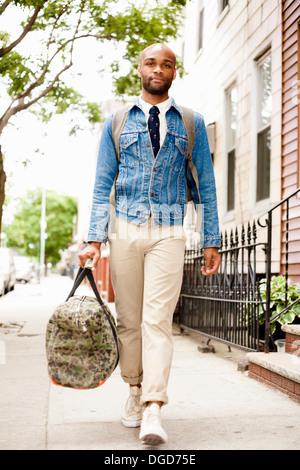 Young man walking down street with holdall - Stock Photo