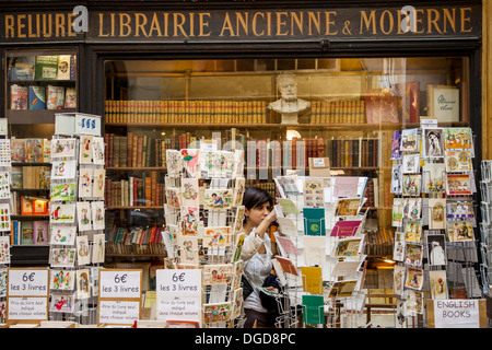 Young woman shopping at an antique bookstore in Passage Vivienne, Paris France - Stock Photo