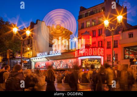 Tourists below the Moulin Rouge (1889), world famous Cabaret, Montmartre, Paris France
