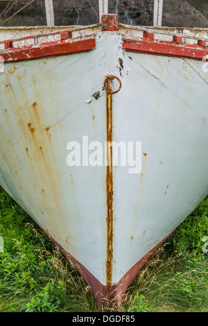 Old wooden fishing boat hull, viewed from the front, in a state of disrepair on Prince Edward Island, Canada. - Stock Photo
