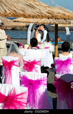 Wedding on the beach of Chinese tourists in the city of  Kamari, on the island Santorini, Cyclades, Greece - Stock Photo