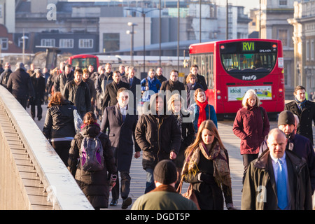 Early morning commuters cross London Bridge for the city on a cold sunny Winter morning - Stock Photo