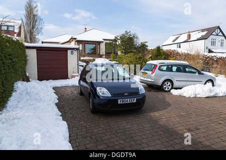 Cars parked on snow cleared drive in front of house - Stock Photo
