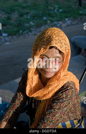 A woman fortune teller wearing a headscarf is working on the riverside promenade in Phnom Penh, Cambodia. - Stock Photo